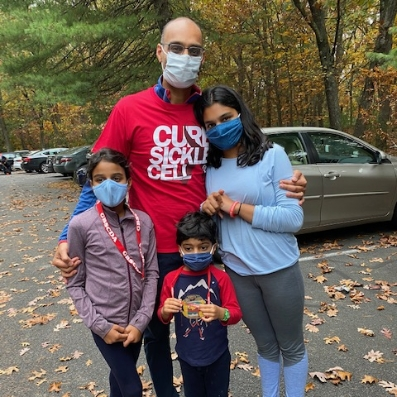 A man and woman and two kids standing in a parking lot with masks on.