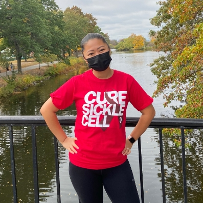 """A woman with her hands on her hips wearing a shirt that says """"Cure Sickle Cell."""""""